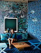 Pattern mix in shades of blue: Young woman on a sofa in the living room with differently wallpapered walls