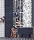Mustermix in Schwarz-Weiß: Junge Frau vor verschieden Bahnen Tapete mit unterschiedlichen grafischen Motiven