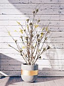 Branches in a concrete flowerpot with golden stripes against a wall of peeled paint