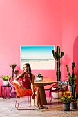 Retro holiday flair with lots of cacti: Young woman sits on Acapulco Chair at a round table in front of a pink wall