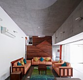 Sofa set with salmon-pink leather covers and arranged scatter cushions in modern living room with exposed concrete ceiling and wood-clad staircase in background