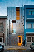 Narrow, three-storey town house with flexible façade made from stainless-steel shutters and illuminated interior at twilight