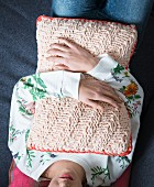 A woman holding a knooked cushion - knitting with a hook