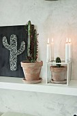 Potted cacti, candlesticks and hand-made string art on black background