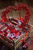 Herz-Kranz aus roten Kunstbeeren, eine Lichterkette und Christbaumkugeln in einer Holzkiste