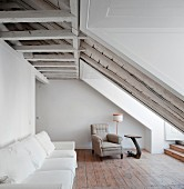 White sofa against wall and traditional armchair in background in converted attic with rustic ambiance
