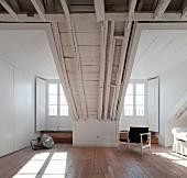 Dachgeschoss mit sichtbarer Holzkonstruktion hell gestrichen mit rustikalem Flair, Sessel vor Terrassentür mit Innen Türlade