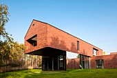 Contemporary, brick house with projecting upper storey in sunny garden