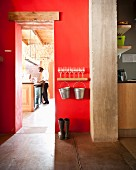Fire-engine-red wall with view of bar counter through narrow doorway