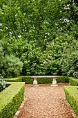 Steinbank in antik griechischem Stil in gestaltetem Garten mit Hecken