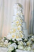 Multi-tiered, white wedding cake romantically decorated with roses