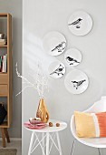 White plates decorated with birds hung on a wall