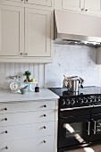 White kitchen with black cooker below wall units with integrated extractor hood
