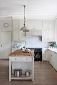 Free-standing island counter below metal pendant lamps in white, country-house kitchen