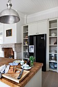Island counter with wooden worksurface and modern, black fridge-freezer integrated into country-house-style fitted kitchen