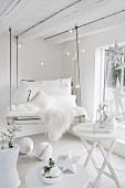 DIY-Palettenschaukel mit weißem Schaffell und Kissen in weißem Raum mit Weihnachtsdeko