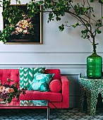 Pink-colored sofas with pillows, next to a leaf branch in a glass vase