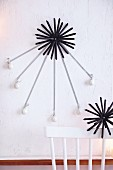 Straw stars hung with mini Christmas baubles as wall decoration