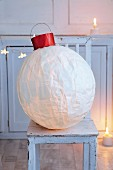 A giant Christmas bauble made from a balloon and silk paper