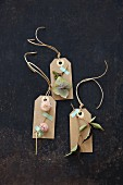 Homemade autumnal gift tags decorated with flowers and leaves
