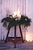 An advent wreath made from pine sprigs and silver, spray-painted plane fruits