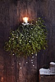Sprigs of mistletoe with mother-of-pearl and a tea light as winter decorations