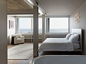 Minimalist bedroom with double bed, white armchair and panoramic window with sea view