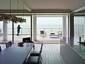 View from dining area with dark table and upholstered chairs through open sliding glass wall to wooden terrace and sea