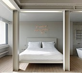 View between pale, steel-beam structure to double bed with white bed linen and illuminated lettering on wall