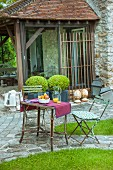 Garden table and chairs in front of potted box balls and roofed terrace