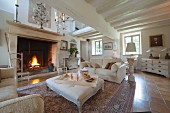 Pale sofa set and ottoman in front of fire in large fireplace in open-plan country-house interior
