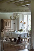 White dining set, chairs with carved backrests and designer table lamps in front of window in background