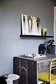 Wooden desk and yellow chair against dark gray wall, black shelf console with modern picture