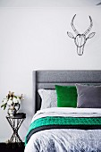 Bed with gray headboard, pillows and bed linen in gray and green, above wall decorative animal trophy made of black wire