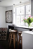 Bunch of tulips on a narrow bar in front of a window, bar stools with cowhide, in rows above pendant lights