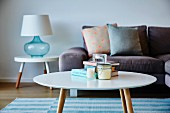 Round retro coffee table in front of sofa with scatter cushions and table lamp on side table