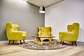 Reading chairs with yellow upholstery and classic coffee table on round flokati rug in corner or room with walls painted different shades