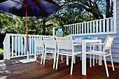White outdoor chairs and table on terrace with blue parasol and white wooden balustrade