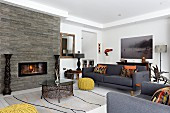 Colourful scatter cushions on grey sofa set and ethnic accessories around fireplace in stone wall