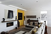 Sofa combination in front of fireplace, yellow wall and artworks
