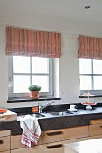 Elegant kitchen counter with dark stone worksurface and integrated double sinks below windows with striped, pastel Roman blinds
