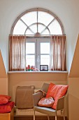 Designerstuhl mit hellbraunem Lederbezug vor apricotfarbener Wand, Fenster mit Oberlicht in Rundgaube
