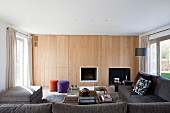 Wood-panelled wall with integrated fireplace and concealed cupboards in living room