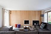 Holzpaneelwand im Wohnzimmer mit eingelassenem Kamin und verstecktem Stauraum