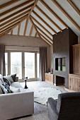 Wohnzimmer unter dem Dach mit Sichtbalken und Einbaukamin