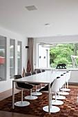 Designerstühle und minimalistischer Esstisch auf Tierfell-Patchworkteppich, Designerleuchte und Kunstobjekte vor Fenster