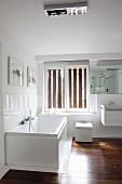 Badezimmerecke mit Fenster, weißer Wanne, WC und Waschbecken in kantigem, modernem Design dazu elegantes Edelholzparkett