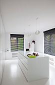 Minimalistischer Ankleideraum mit zentralem weißem Schubladenschrank, weissen Designerleuchten und Fenstern mit schwarzen Jalousien