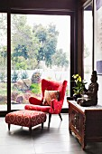 Elegant red reading armchair and footstool in front of floor-to-ceiling glazing with a garden view