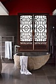 Natural stone bathtub in front of carved Asian-style shutters